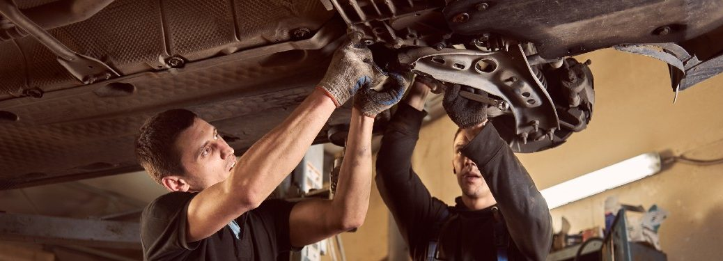 Mechanics repairing the transmission in a vehicle