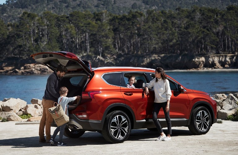 Rear passenger angle of an orange 2020 Hyundai Santa Fe with its liftgate open and a family getting camping supplies