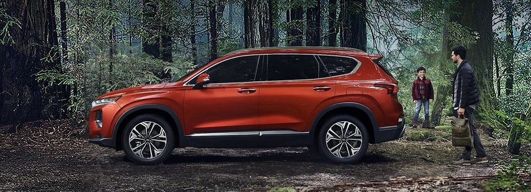 Driver angle of an orange 2020 Hyundai Santa Fe parked in a forest with a dad and boy near it