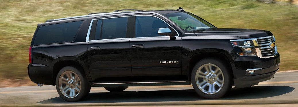 Passenger angle of a black 2020 Chevrolet Suburban driving on a road