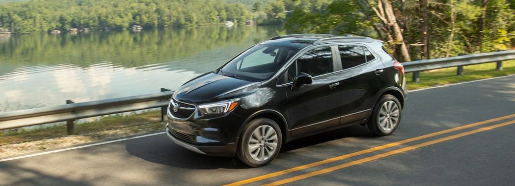 Front driver angle of a black 2020 Buick Encore driving near a lake