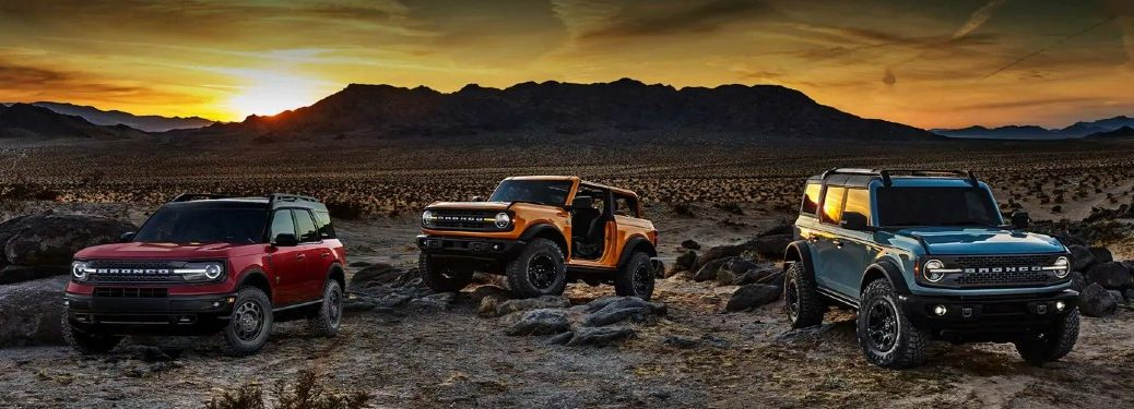 Three 2021 Ford Bronco and Ford Bronco Sport vehicles parked off-road with a sunset in the background