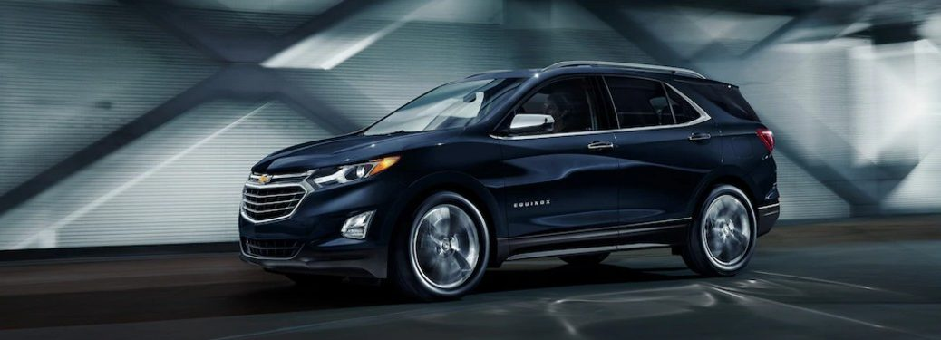 Front driver angle of a dark blue 2020 Chevrolet Equinox driving down a road