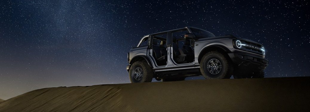 Silver 2021 Ford Bronco parked in a desert under a starry night