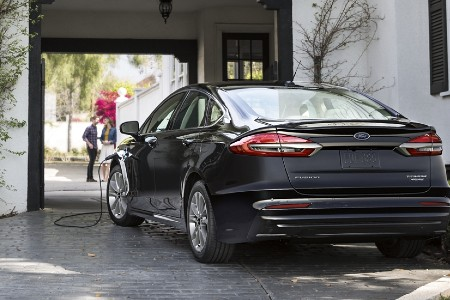 Rear driver angle of a black 2020 Ford Fusion plug-in hybrid charging at a home