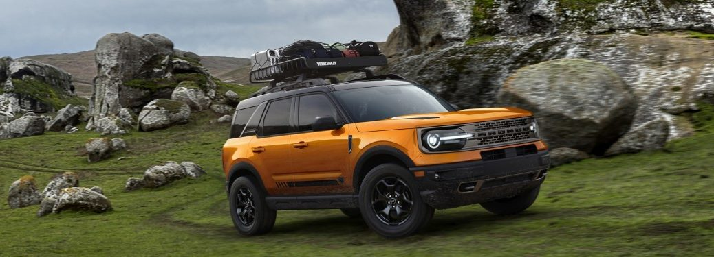 Front passenger angle of an orange 2021 Ford Bronco driving off-road