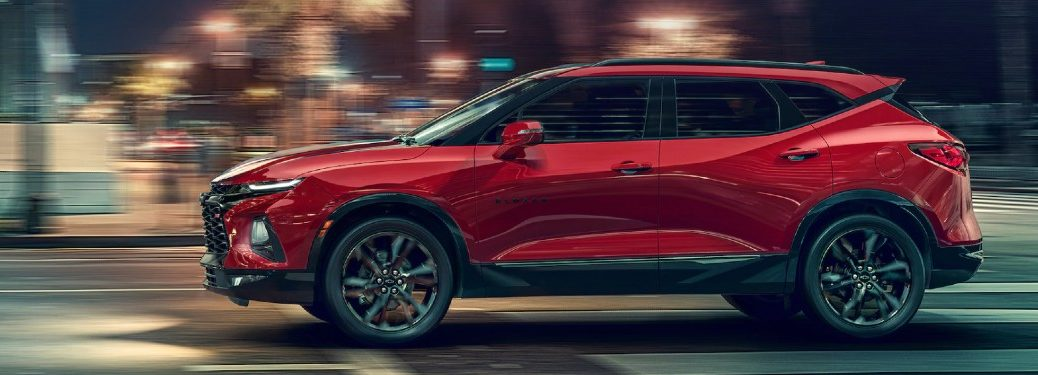 Driver angle of a red 2021 Chevrolet Blazer driving in a city