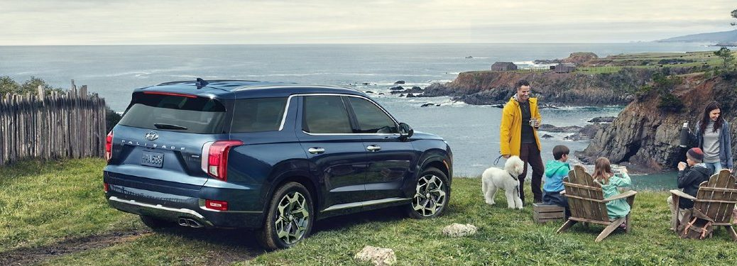 Rear passenger angle of a blue 2021 Hyundai Palisade parked near an ocean with a family sitting outside by it