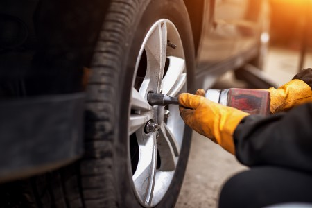 Close up of a mechanic replacing a tire on a car