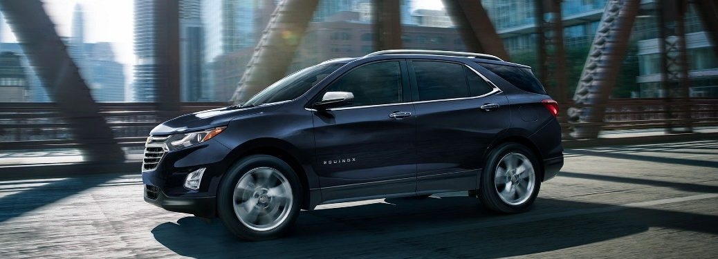Front driver angle of a blue 2021 Chevrolet Equinox driving on a bridge