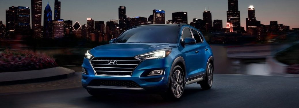 Front driver angle of a blue 2021 Hyundai Tucson with a city in the background