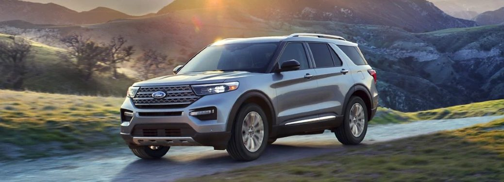 Front driver angle of a white 2021 Ford Explorer driving on a road with a sunset in the background