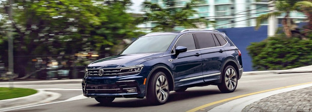 Front driver angle of a blue 2021 Volkswagen Tiguan driving in a city