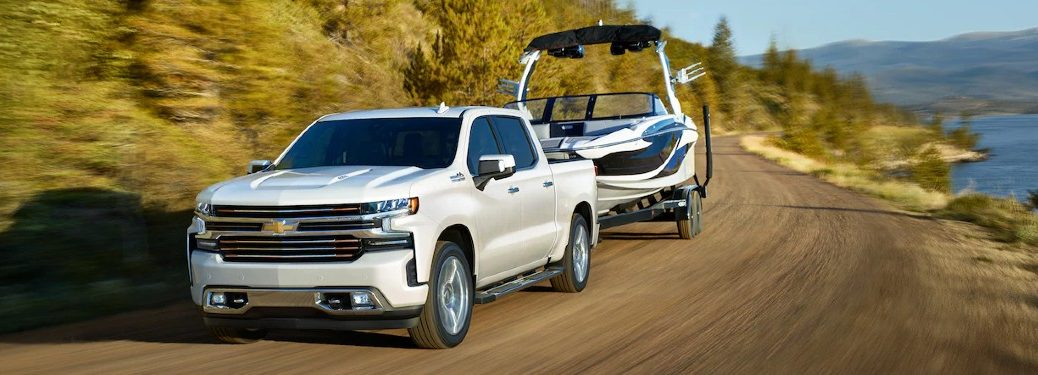 Front driver angle of a white 2021 Chevrolet Silverado 1500 towing a boat