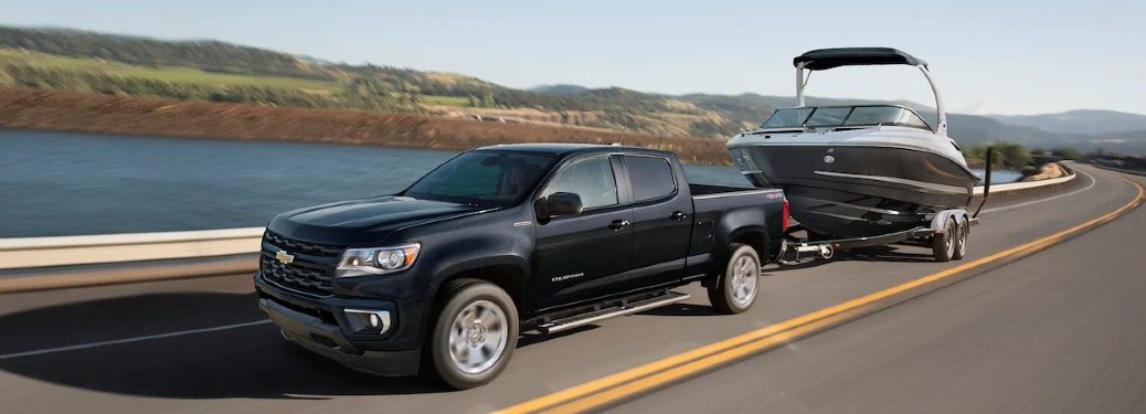 Front driver angle of a black 2021 Chevrolet Colorado towing a boat