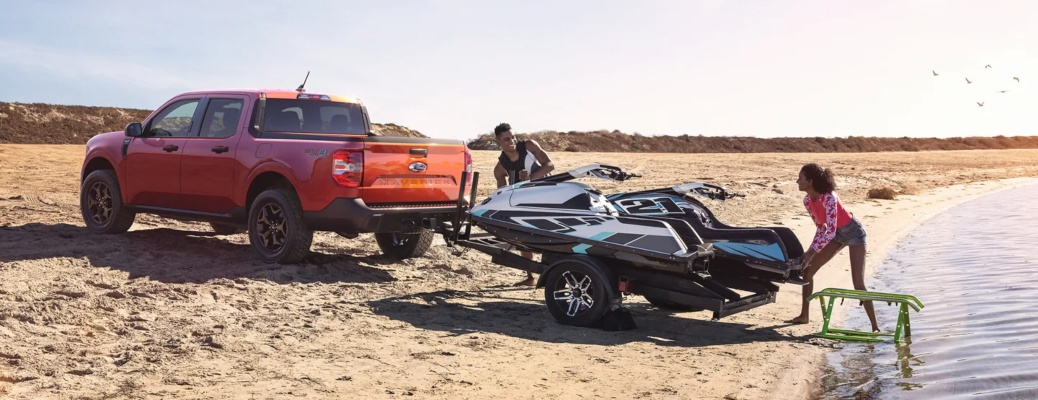 2022 Ford Maverick red side view backing jet-skis into water