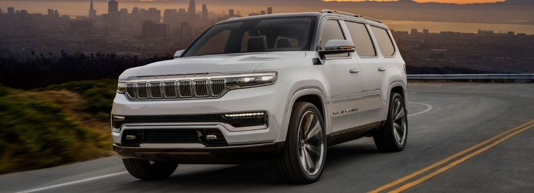 White 2021 Jeep Grand Wagoneer Concept Driving at Dusk with City Skyline in the Background