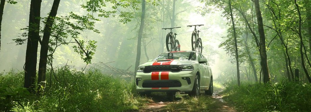 2021 Dodge Durango white exterior with red stripes front fascia driving in forest with bikes on roof rack