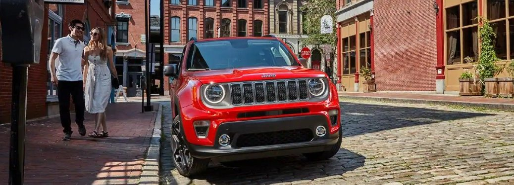 red 2021 Jeep Renegade front fascia parked on brick road in city couple walking past on sidewalk
