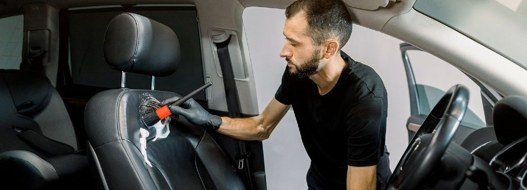 worker cleaning vinyl driver seat of vehicle