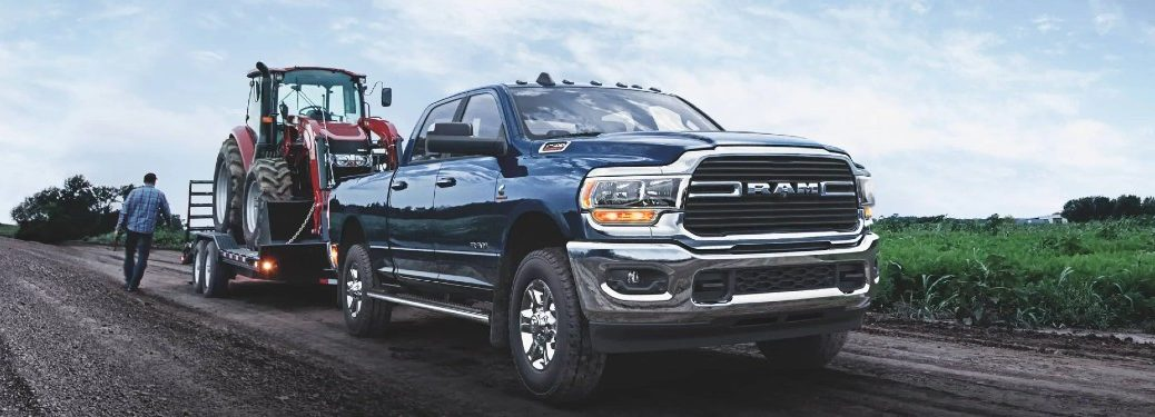blue 2021 Ram 2500 front fascia passenger side parked on dirt road with small tractor on trailer