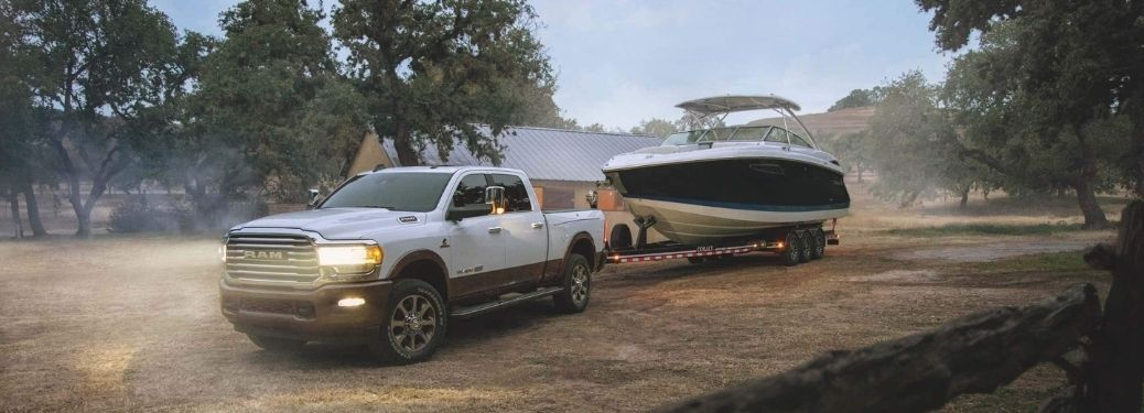 2021 Ram 2500 towing a proportionately large boat passing through a farm.