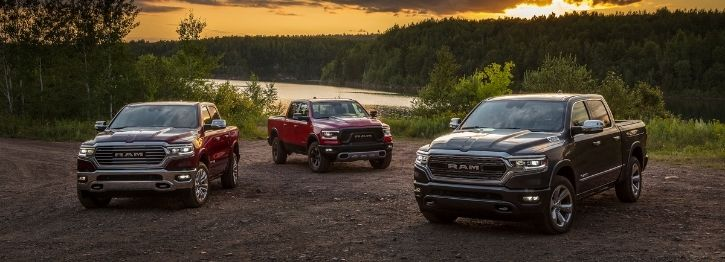 Three 2022 RAM 1500s parked in a forest area