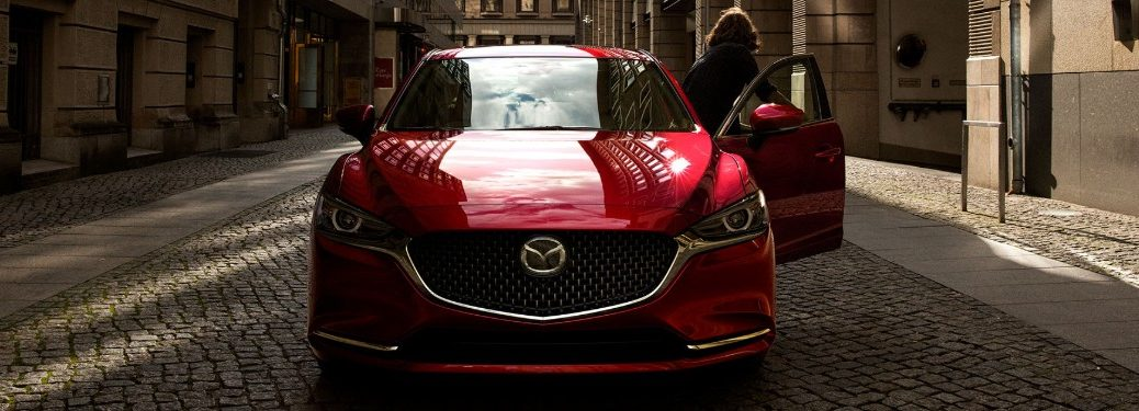 Front view of a red 2019 Mazda6 with a woman exiting through the driver door
