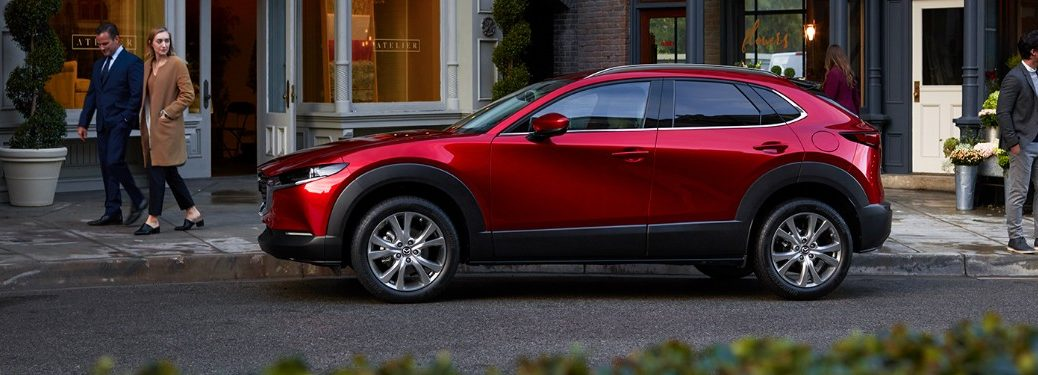 Driver angle of a red 2020 Mazda CX-30 parked on the side of a street with people looking at it