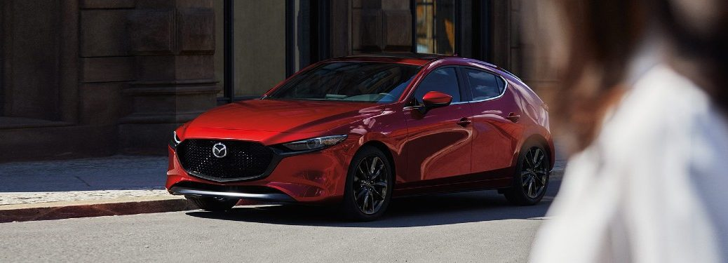 Front driver angle of a red 2020 Mazda3 hatchback with a person in the foreground