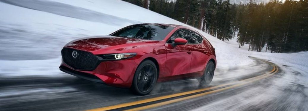 Red 2020 Mazda3 hatchback driving during the winter
