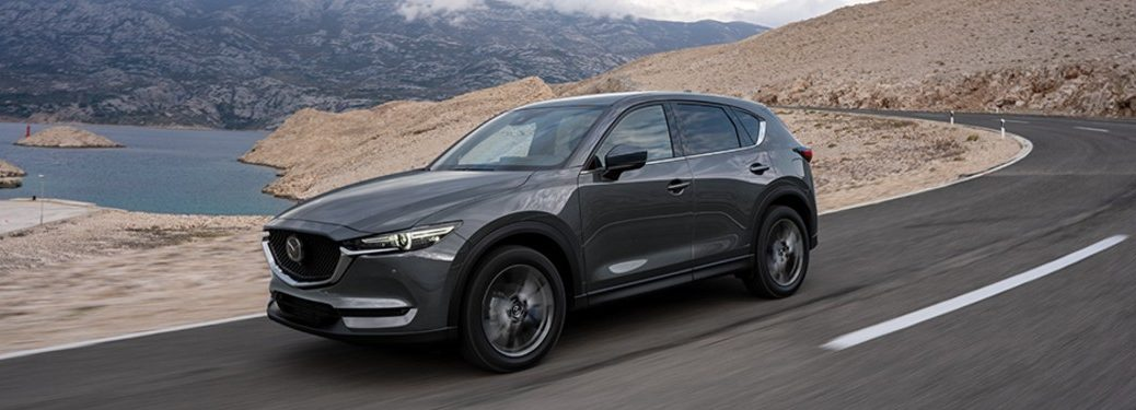 Front driver angle of a grey 2020 Mazda CX-5 driving near water