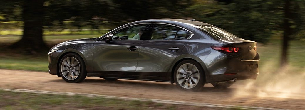 Rear driver angle of a gray 2020 Mazda3 sedan driving on a dirt road