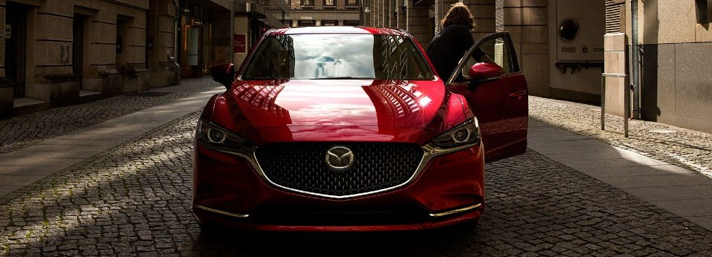 Front angle of a red 2020 Mazda6 with a woman exiting it