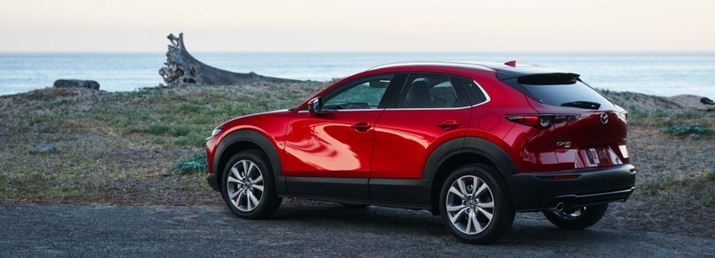 Rear driver angle of a red 2021 Mazda CX-30 parked near an ocean