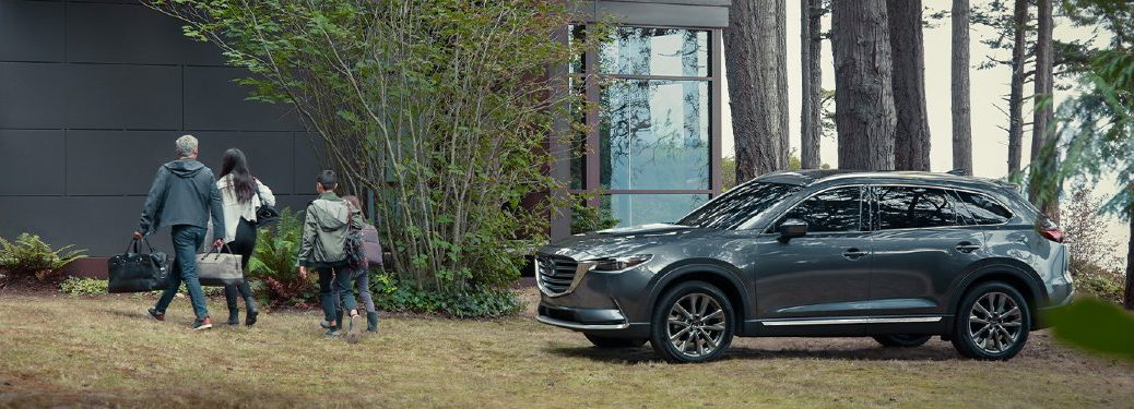 Driver angle of a grey 2020 Mazda CX-9 with a family walking away from it
