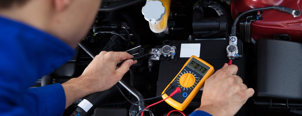 man testing a car battery with a multi-meter