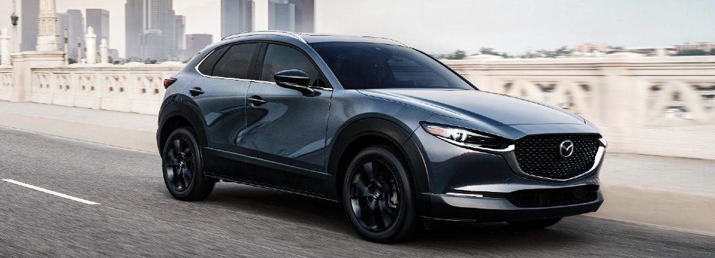 Front passenger angle of a grey 2021 Mazda CX-30 driving on a highway