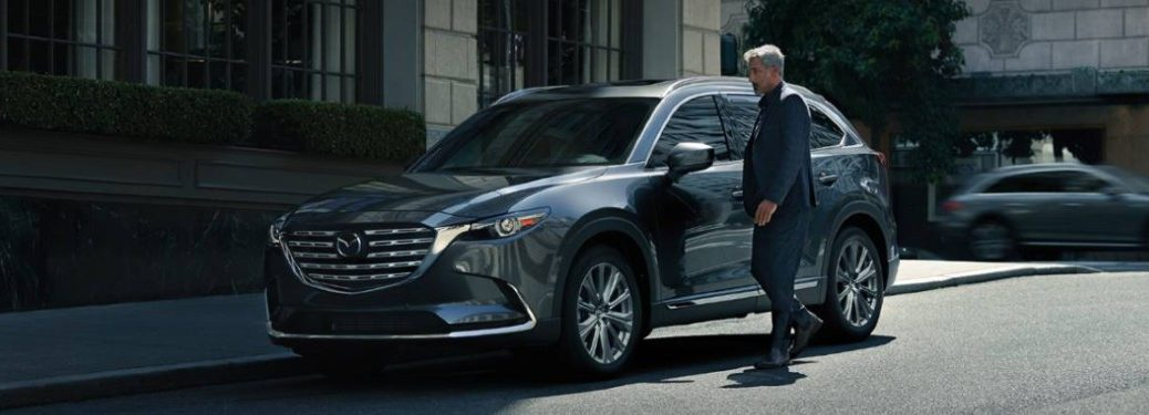 Front driver angle of a grey 2021 Mazda CX-9 with a man standing by its driver's door