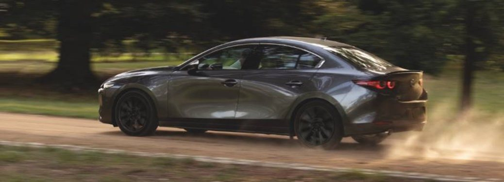 Driver angle of a grey 2021 Mazda3 driving on a dirt road