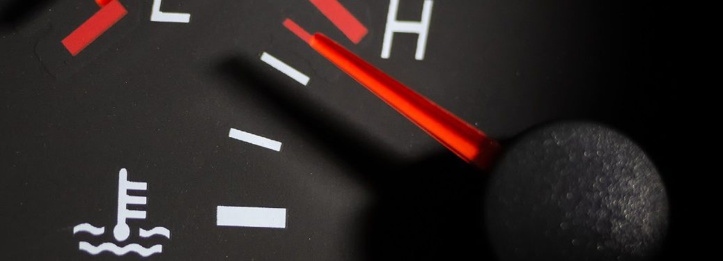 Close up of the temperature gauge in a car spiking to the red