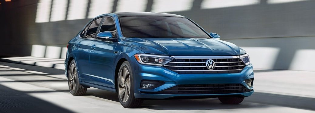 Front passenger angle of a blue 2019 Volkswagen Jetta driving down a road
