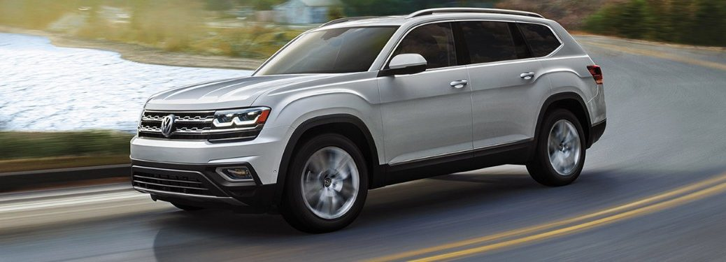 Front driver angle of a white 2019 Volkswagen Atlas driving on a road by a lake