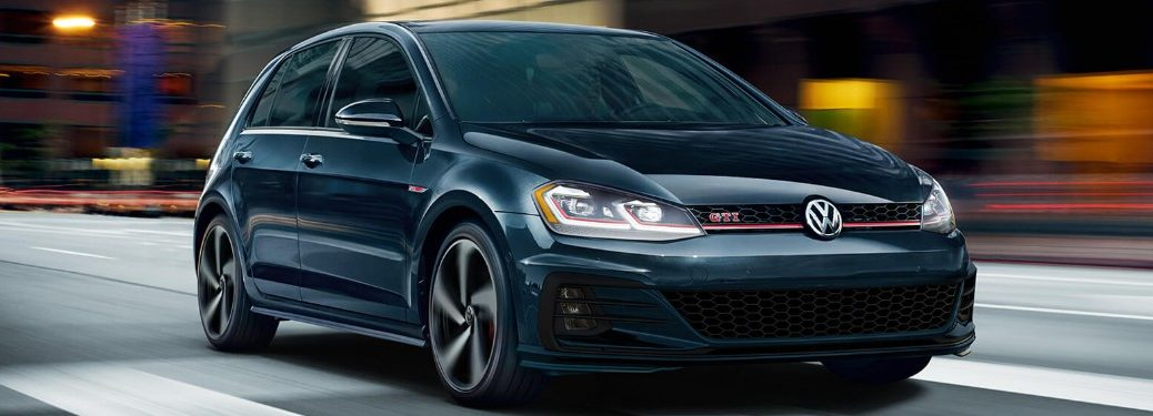 Front passenger angle of a blue 2019 Volkswagen Golf GTI driving down a city street