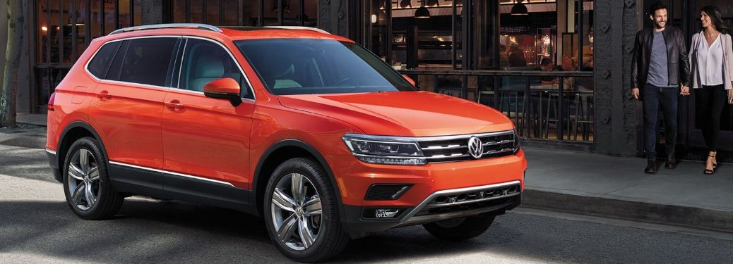Front passenger angle of an orange 2019 Volkswagen Tiguan parked on a street with a couple walking towards it