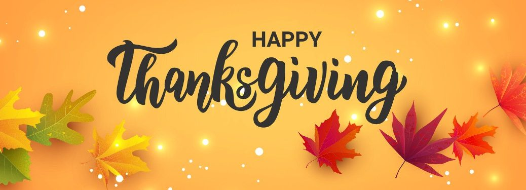 """Leaves and lights on an orange background with the text """"Happy Thanksgiving"""""""