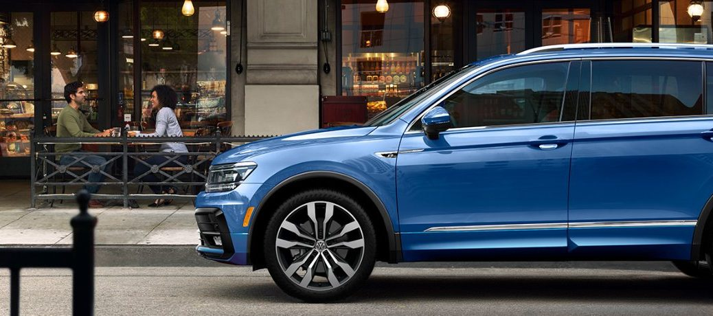 Driver angle of a blue 2020 Volkswagen Tiguan parked by a deli