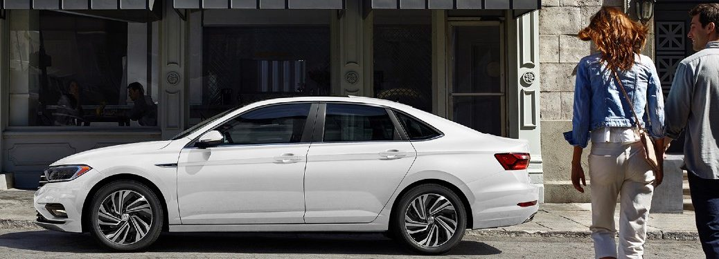 Driver angle of a white 2020 Volkswagen Jetta with two people walking towards it