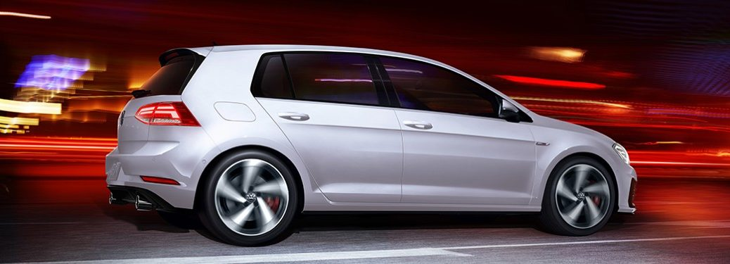 White 2020 Volkswagen Golf GTI driving in a city at night