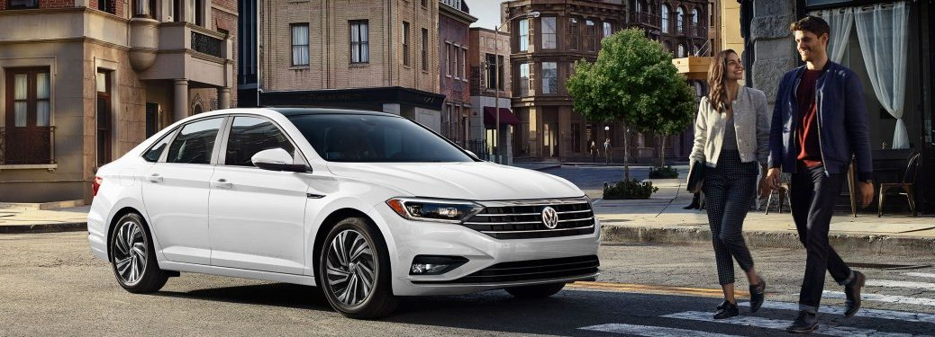 Front passenger angle of a white 2020 Volkswagen Jetta with people crossing the street in front of it